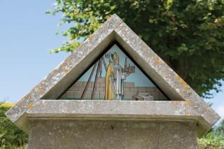The plaque to St Osmund near the church gate, St Osmunds Church,Osmington