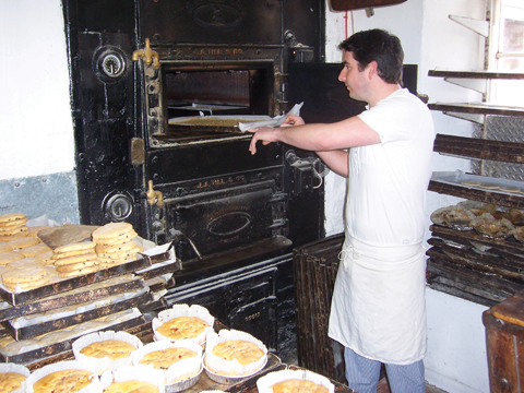 Steven Oxford puts another batch of flapjacks into the venerable oven at the bakery in Alweston