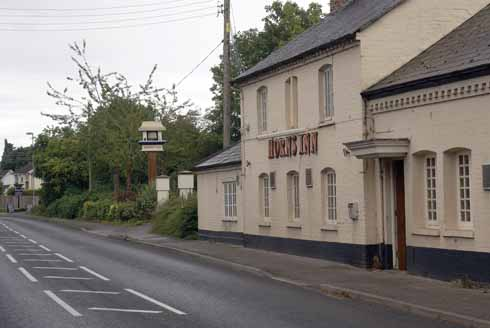 The main entrance of the Horns Inn had moved to the extension building to the right. Although the pub no longer has an Inn sign hanging over the road – which wouldn't be terribly lorry-friendly – the upright for the cantilevered wrought iron sign support is still in place. The original sign bears the then publican's name, Albert Cutler, on a plaque visible in the older picture