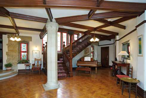 A view of the main hall added by E T Sturdy, showing the splendid staircase, examples of the coloured glass, and some of the furniture acquired by the present owners in keeping with the style of the house
