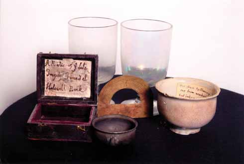 A collection of wreck relics: brass protractor from the ship's chart room, apothecary's cup and 18th-century wine glasses