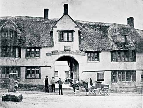 The White Horse at Maiden Newton, with the stub of the market cross at the left. When this photograph was taken – probably in the 1870s, but possibly the 1860s – it was still a super building with its original stone windows, and still thatched.