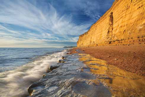 The towering golden sandstone cliffs between Burton Bradstock and West Bay are familiar landmarks of the Jurassic Coast