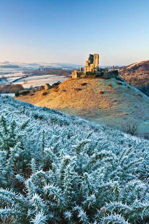 The crumbling ruins of Corfe Castle are positioned in a strategic gap in the Purbeck Hills. Both East Hill and West Hill provide stunning views of the majestic Dorset landmark.