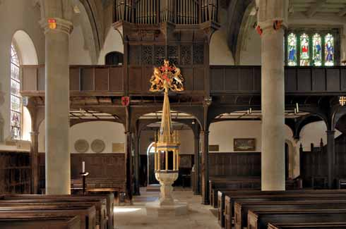 The west gallery, in dark oak, houses the organ and has seating for the choir and bell ringers