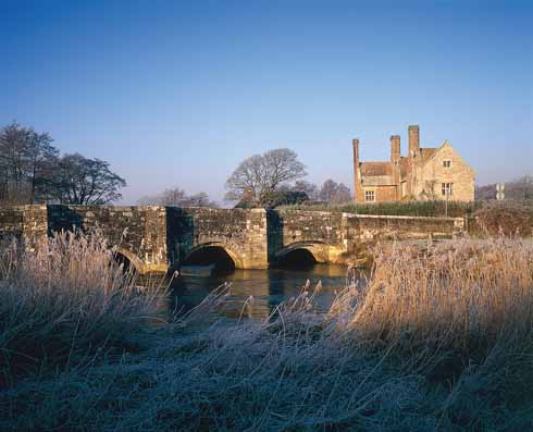 The Wellbridge Manor of Hardy's novel, Woolbridge Manor House, shown with the Frome and the Elizabethan stone bridge, parapets somewhat battered by World War 1 tanks, standing in the foreground