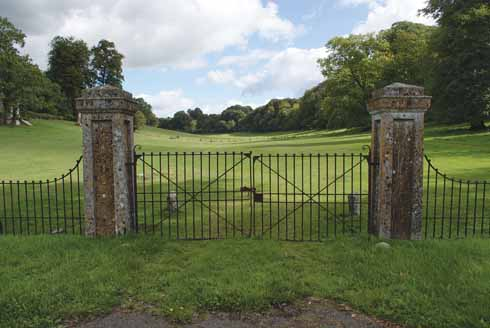 Parkland protected by iron gates just opposite the 17th-century Manor House in Piddletrenthide