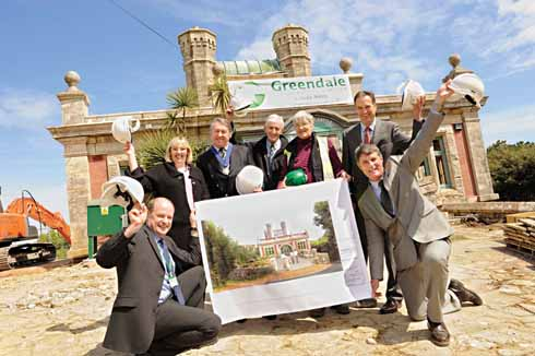 Before work started: Durlston castle sits behind a jubilant group of contractors and stake-holders in the project holding an artist's impression of the new entrance.