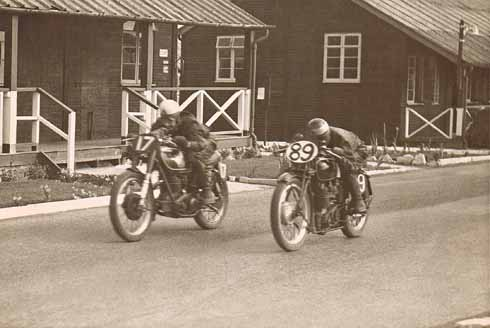 Two riders rush past the old wooden army huts at Blandford Camp in a 1950s race meeting