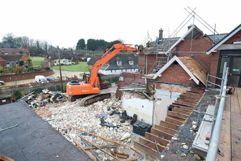 The first stage of building with existing outbuildings being demolished to make way