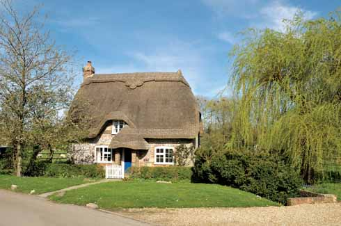 A most attractive brick and flint thatched cottage sits lightly within the rural landscape