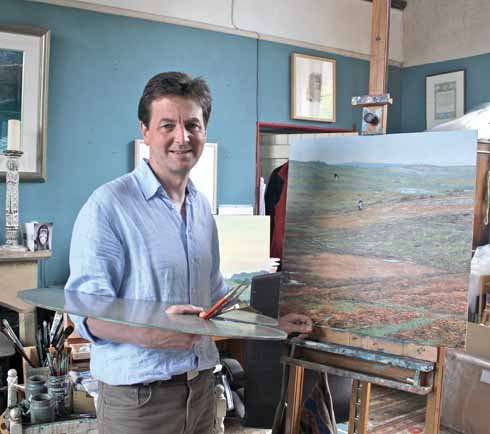 Andrew Stock in his studio, at work on a painting