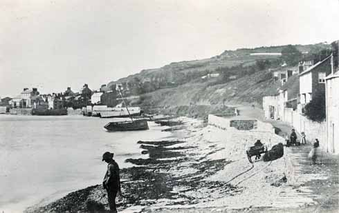 The Walk in 1857, with a wrecked ship driven out of the Cobb by a storm. Cobb Hamlet (in the background), and West Fort still survive.