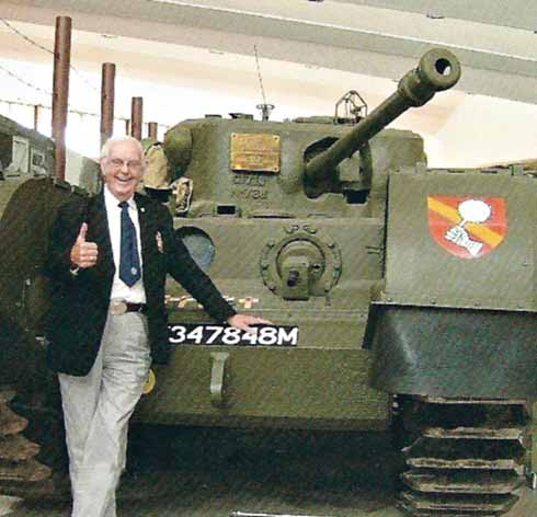 Ray Sansom in front of a Churchill tank at Bovington Tank museum