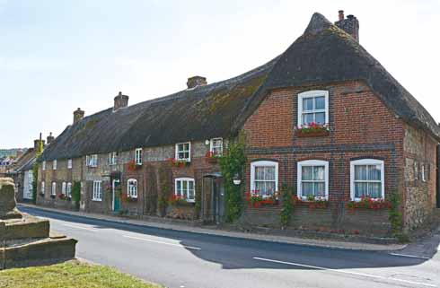 A terrace of brick and flint cottages opposite the cross