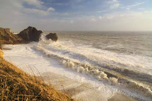 This was from the first set of storms in February 2014. As Andy recalls: 'This shot is practically at low tide, despite the foam on the beach reaching the cliffs. There was a boulder – about the size of a commercial wheelie bin – being tossed in onto the beach and then out. In the morning, the waves (not the spray, but the waves) had been hitting the cliffs up to the level of the grass. The beach was completely flat after the storms. '