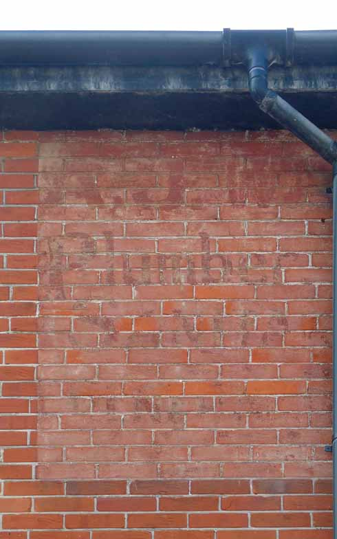 Augustus J Warren's sign has been half covered, while the rest has faded with time