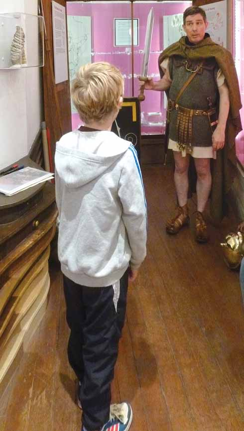 A Roman legionary talks to a young visitor to the museum