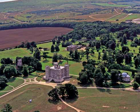 An aerial view of Lulworth Castle. To the left is the parish church of St Andrew, to the right the Roman Catholic Chapel of St Mary. Lulworth Castle House is behind the castle, with the Army ranges in the background.