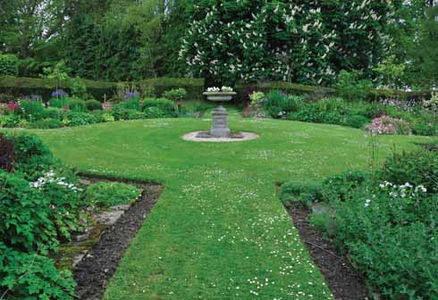Mirroring the circular herbaceous borders elsewhere, the garden also has circular areas surrounded by colourful borders