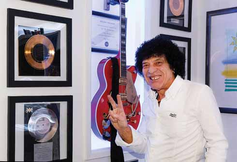 Ray at home with the wall of gold and silver disc awards that Britta made for him. A PRS Iconic Song Award forms the centrepiece with a Grestch Nashville guitar