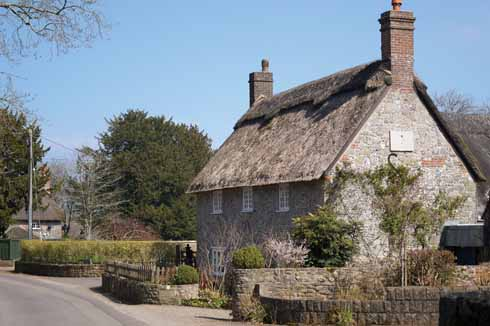 A thatch lightly worn atop brick, stone and flint walls is typical of the vernacular style