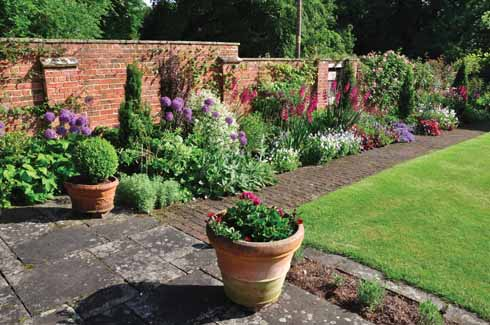 From the York stone terrace in front of the house a brick path leads down past a colourful mixed border