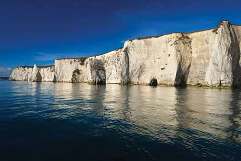 This early autumn shot at Old Harry Rocks in early morning sunshine looks towards Handfast Point and the Pinnacles