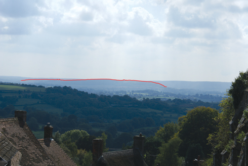 Often missed by the casual observer is the fact that Hambledon Hill is hidden on the horizon when taking in the view from the top of Gold Hill; here it is outlined in red