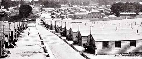 Dorchester prisoner of war camp's lines of wooden huts, a few inmates standing at the door of the nearest
