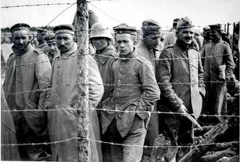 By the camp's perimeter wire a group of German prisoners glower at the camera. One man has retained his helmet from the trenches