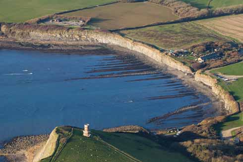 The characteristic seaward lines of Kimmeridge Bay with  the Landmark Trust's Clavell Tower, which is available for holiday lets, in the foreground. It was disassembled from the edge of the crumbling cliff and rebuilt 25 metres further inland. In the distance is a nodding donkey oil pump.