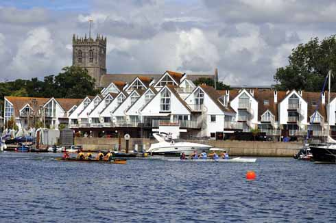 Two crews fight it out in one of the regatta races in the shadow of the Priory