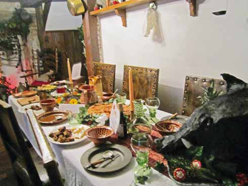 The table in the main room laid up for a Christmas feast, including a specially constructed boar's head. The decorations feature holly and ivy, but no Christmas tree, streamers or glitter, all of which came well after the Tudor period.