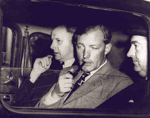 Heath insouciantly smoking his pipe while he is flanked by detectives. Heath was described as the psychopath's psychopath.