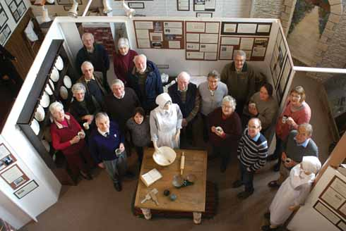 Seventeen of the many Beaminster Museum volunteers  in the Life Below Stairs exhibition space at the centre of the main exhibition space