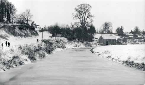 The Stour frozen over with the mill in the background