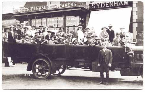 A charabanc of tourists outside Sydenham the steam packet trip agent and 'fancy bazaar'