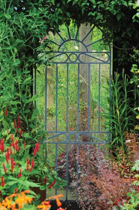 A tall mirror set behind what appears to be a gate suggests additional distant interest while in fact it is a reflection of the garden from which it is viewed