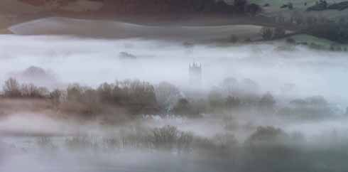 The tower of St Mary's church in Cerne Abbas is just visible in the  half-light just after dawn