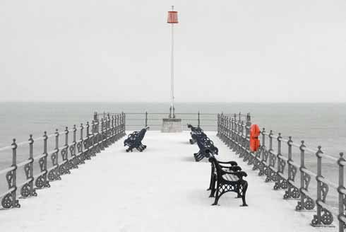 The snow on the banjo jetty at Swanage makes the red of the lifebelt holder on the right of the shot and the pier marker in the top middle of the shot really stand out