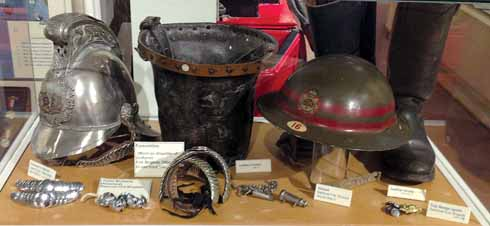 Helmets, a bucket and other memorabilia in the Fire exhibition at the museum