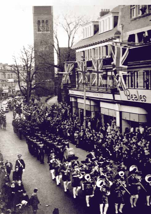 The parade passes the temporary premises on Old Christchurch Road from which Beales operated after its flagship store was bombed out in World War 2. The tower is that of Holy Trinity Church, which was demolished after an arson attack.