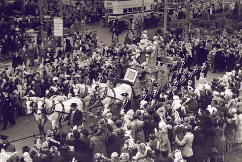Father Christmas arrives in style with a sailors' escort. Note well his book containing the names of 'Good Girls and Boys' and also the crowd standing six deep along the route of the procession