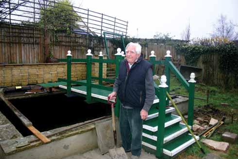 The seven-foot deep fish pond in Roy's garden, complete with wooden footbridge