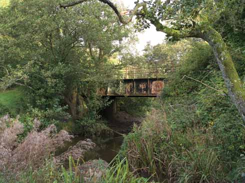 The line from Maiden Newton to Bridport was officially opened in 1857. The iron bridge depicted here crosses the River Hooke close to the dismantled Toller station.