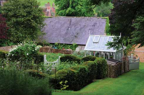 A view of the garden, greenhouse and rose garden with the house in the background.