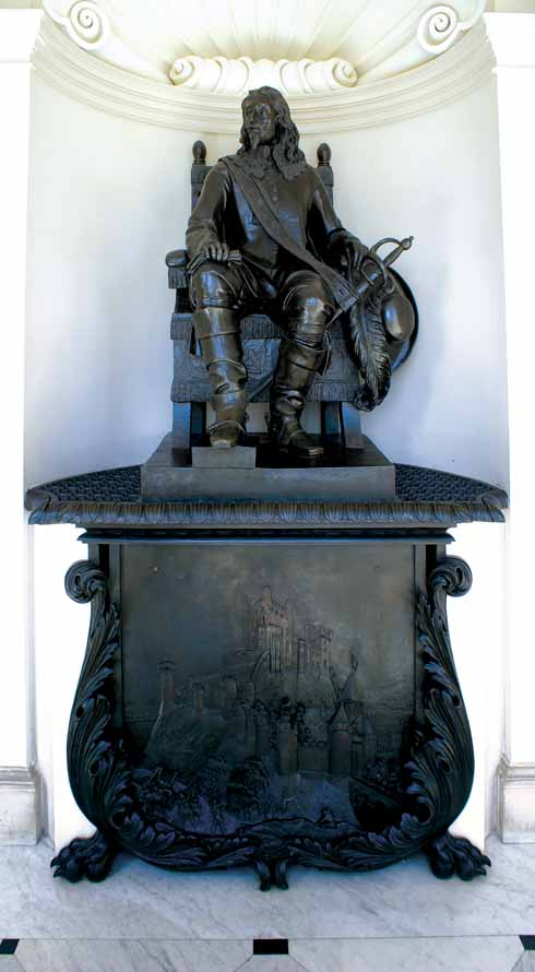 The statue of Charles I on the main staircase of Kingston Lacy, with the siege of Corfe Castle shown on the shield below