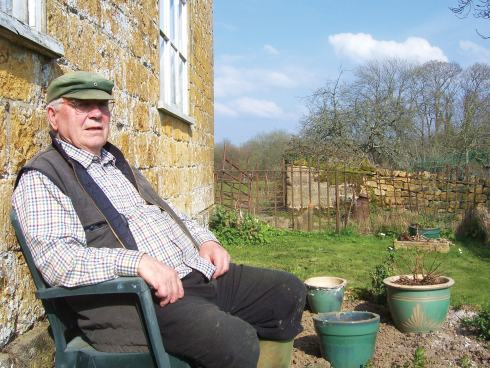 Les relaxes outside the farmhouse he has lived in for over fifty years